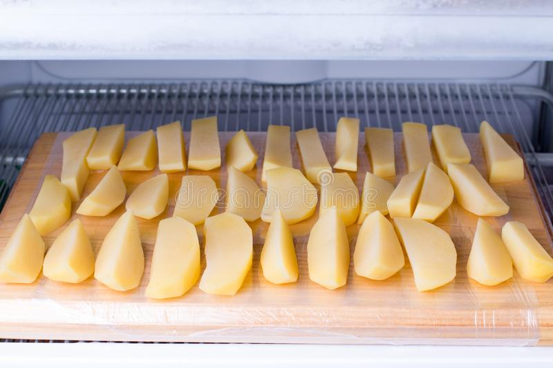 Frozen potatoes on the chopping board in the freezer. Frozen food stock images