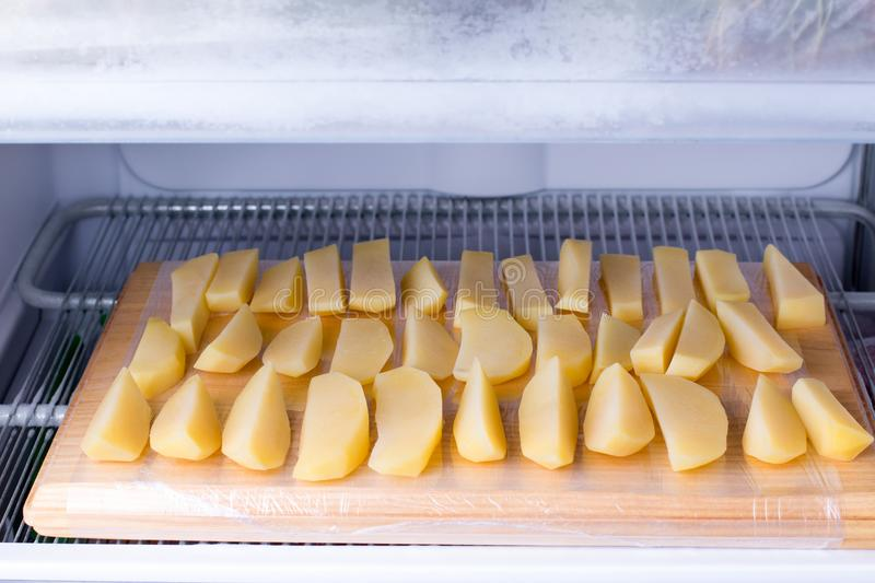 Frozen potatoes on the chopping board in the freezer. Frozen food royalty free stock photo