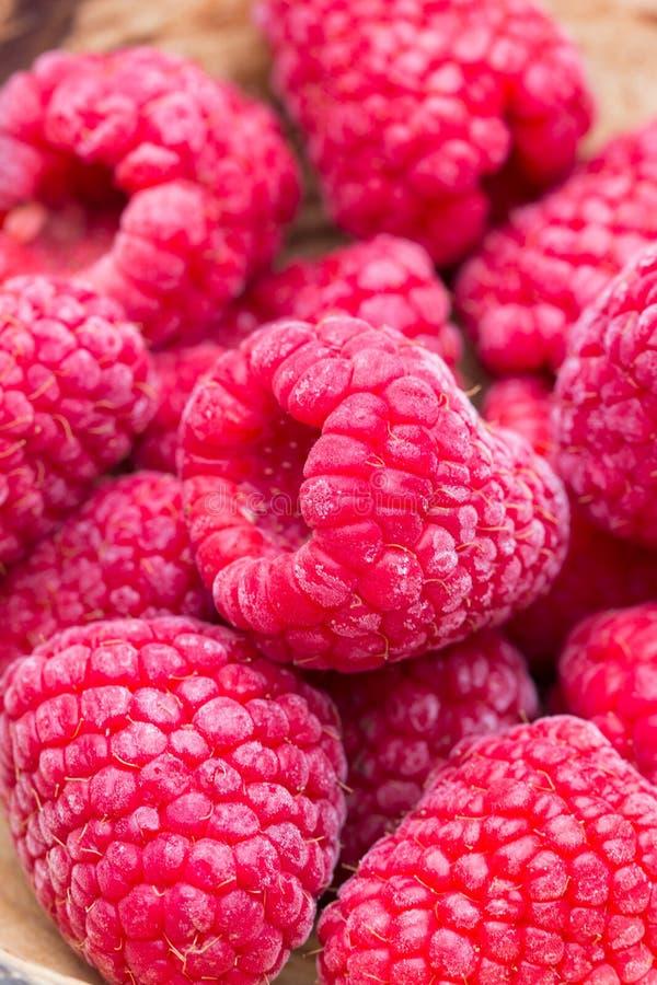 Frozen raspberries on wooden background stock image