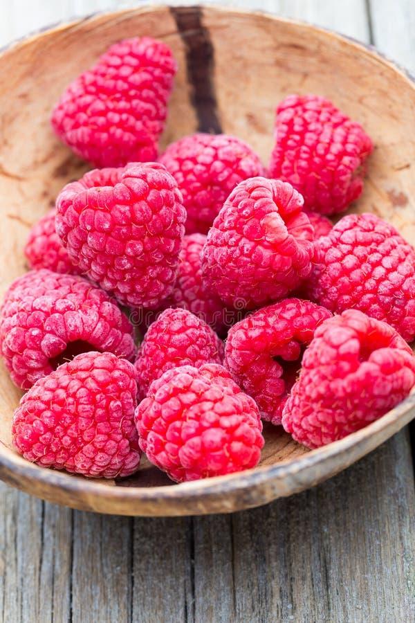 Frozen raspberries on wooden background. stock photos