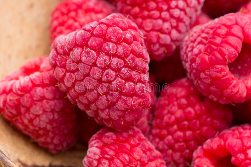 Frozen raspberries on wooden background. stock photo