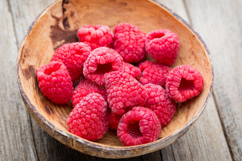 Frozen raspberries on wooden background royalty free stock photography