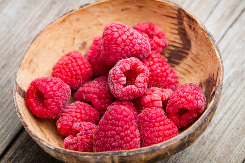 Frozen raspberries on wooden background. royalty free stock photos