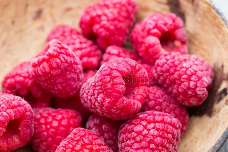 Frozen raspberries on wooden background. stock images