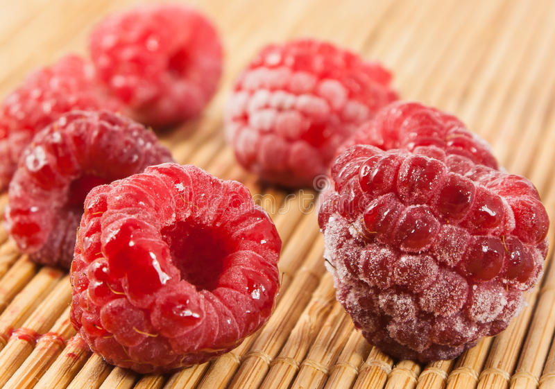 Frozen raspberries on wooden background royalty free stock photos