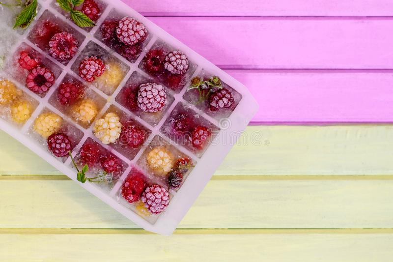 Frozen red and yellow raspberries in ice cubes on a wooden background royalty free stock photos