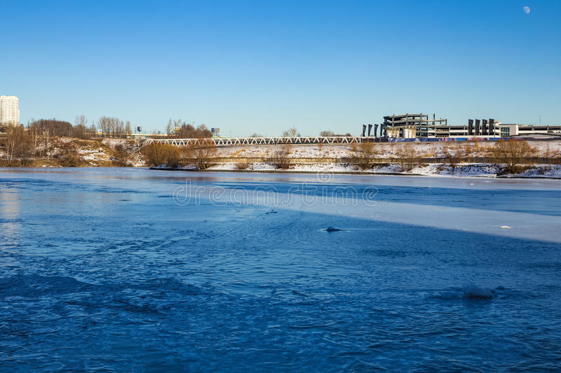 Frozen river in city limits. Frozen river in the city, the moon on clear blue clear sky royalty free stock photo