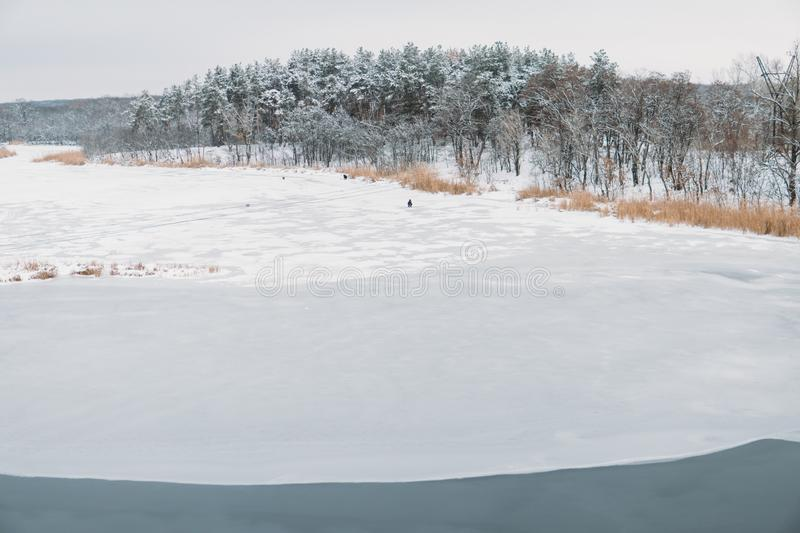 Frozen river in the middle of the forest with a fishermanÑŽ. Frozen river in the middle of the forest with a fisherman royalty free stock photos