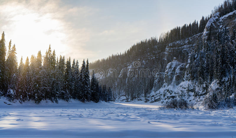 Frozen river at rocky shore stock image