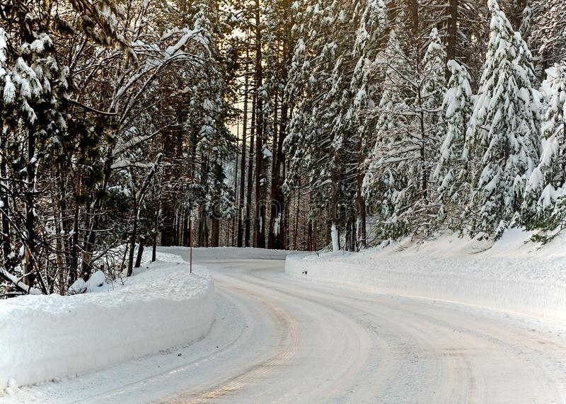 Frozen road highway 120 towards Yosemite. Unplowed mountain road highway 120 towards Yosemite, California, USA, on a winters day featuring snow on the road as a stock photos