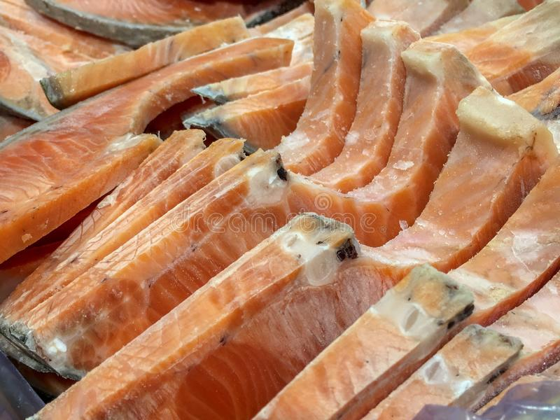 Bunch and pile of cut frozen orange salmon at the supermarket grocery store. Close up shot. royalty free stock image