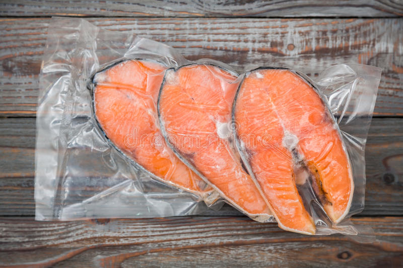Frozen salmon fillets. In a vacuum package wood table royalty free stock photos