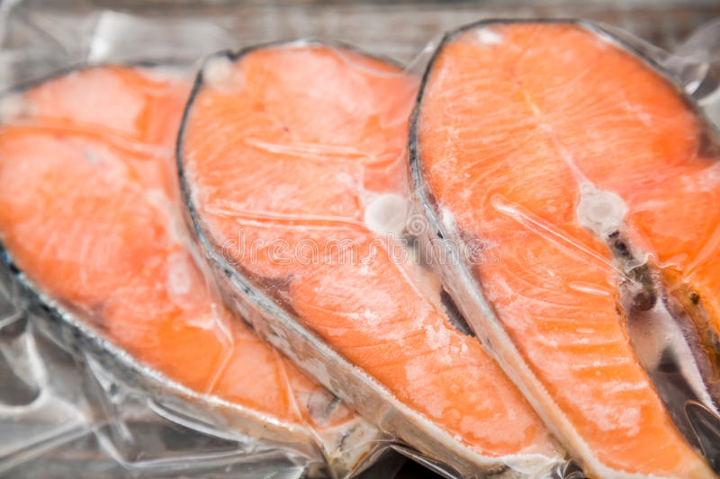 Frozen salmon fillets in a vacuum package. Wood table royalty free stock images