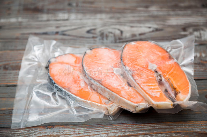 Frozen salmon fillets in a vacuum package. Wood table stock images