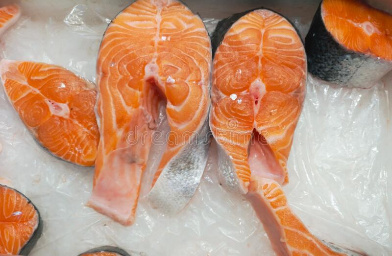 Frozen salmon fish with ice sold in a large grocery shopping center stock photos