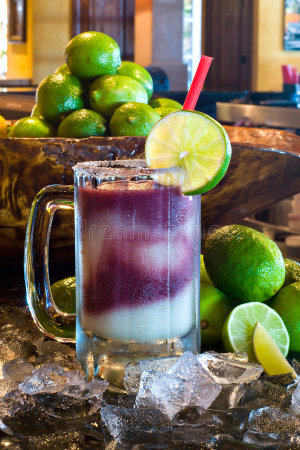 A Frozen Sangria Margarita. Frozen Margarita with Sangria on bar with ice and limes in background medium DOF royalty free stock image