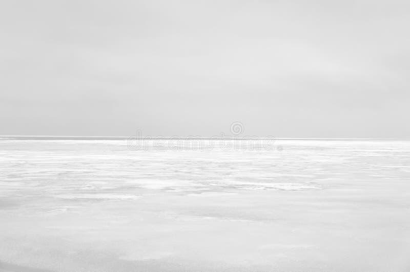 Frozen sea water and gray sky over horizon. Nature background. Frozen sea water and gray sky over horizon. Landscape at winter season. Image in light gray stock photography