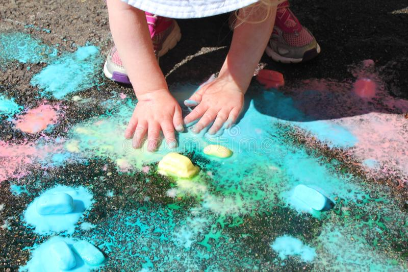 Frozen sidewalk paint preparation and use in a daycare/home school setting.  royalty free stock images