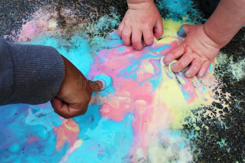 Frozen sidewalk paint preparation and use in a daycare/home school setting.  royalty free stock photos