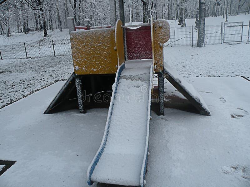 Frozen slide toy kids sad nature winter public parc. Frozen slide toy kids Winter panorama snow everywhere sad nature view public parc stock photography