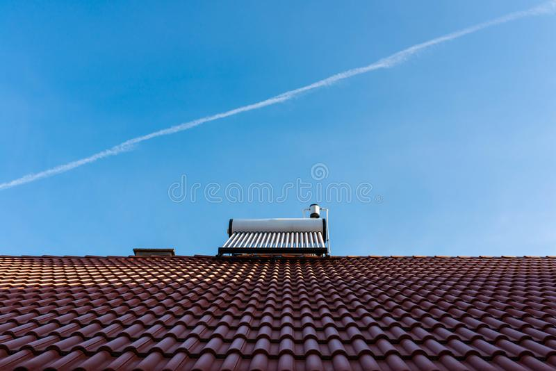 Frozen solar water heater boiler on rooftop, passing aeroplane. Blue sky background royalty free stock photography