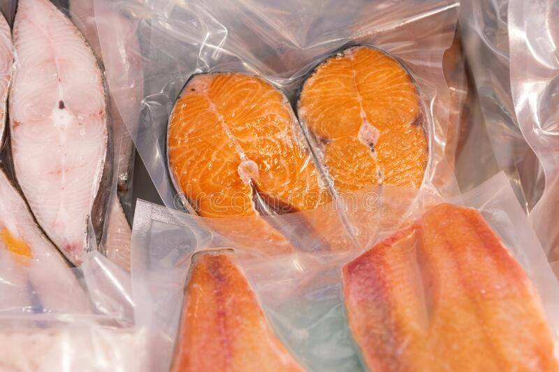 Frozen steaks of red fish. Fish packed vacuum bags. Freezer shop window royalty free stock images