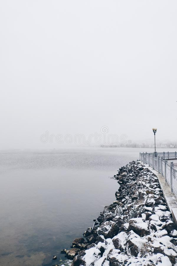 Frozen stones near the lake in winter day. Foggy royalty free stock photo