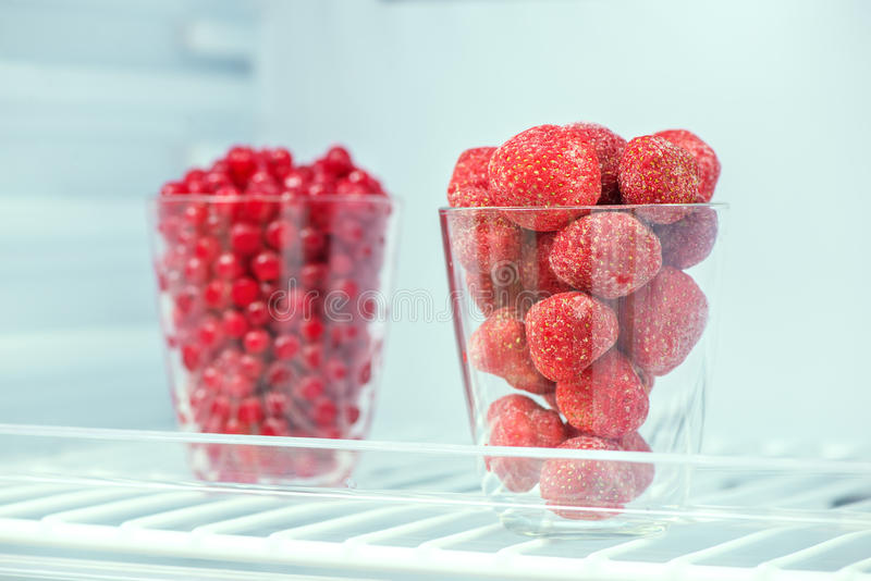 Frozen strawberries and red currants. On a shelf in the freezer closeup, preparations for the winter stock photography
