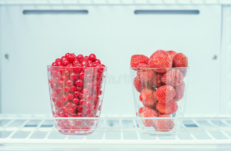 Frozen strawberries and red currants. On a shelf in the freezer closeup, preparations for the winter, the ingredients for the sorbet royalty free stock photography
