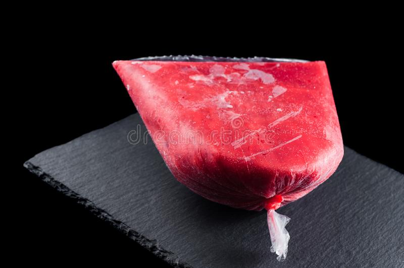Frozen strawberry raspberry puree in a plastic bag on a stone plate on a black background, isolate royalty free stock image