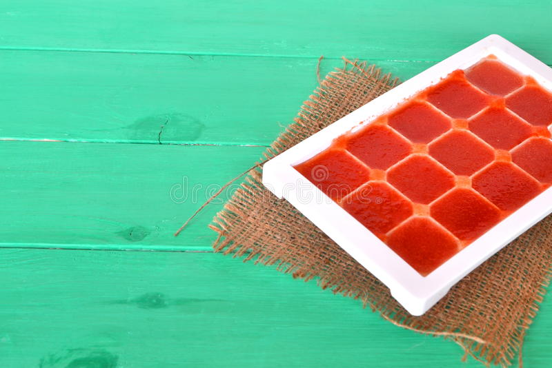 Frozen tomato juice cubes in a plastic form. Life hack, easy way to store vegetables. Frozen tomato juice. Juice cubes royalty free stock photos