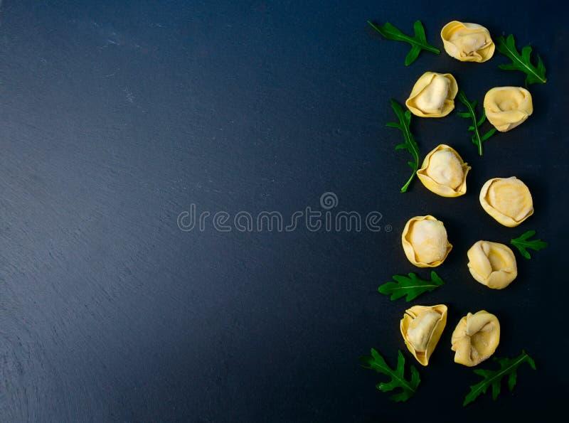 Frozen tortellini on the black background. Italian tortellini with fresh ricotta leaves on a black stone board. stock image