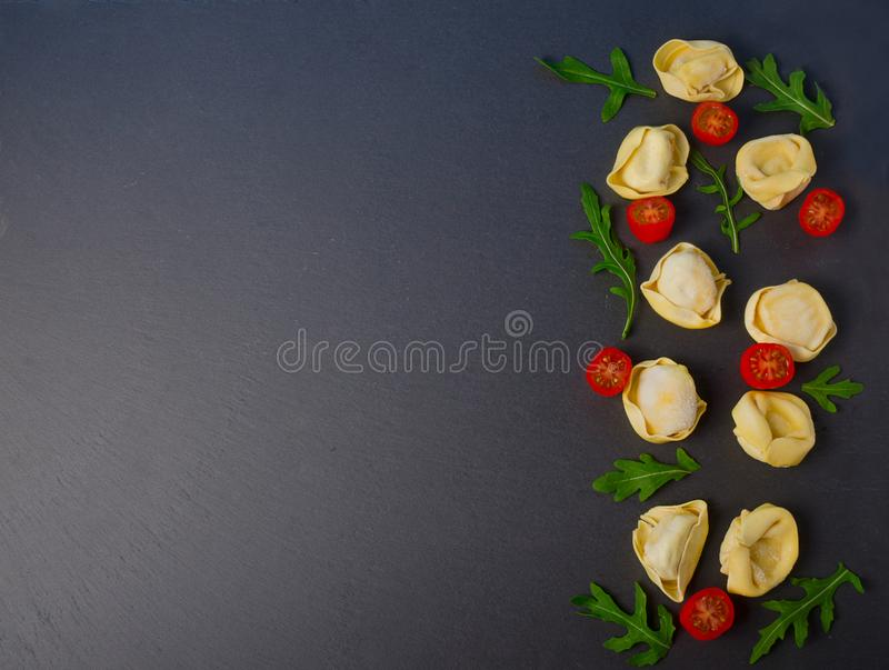 Frozen tortellini on the black background. Italian tortellini with fresh ricotta leaves and tomatoes on a black stone board. Top view stock photo