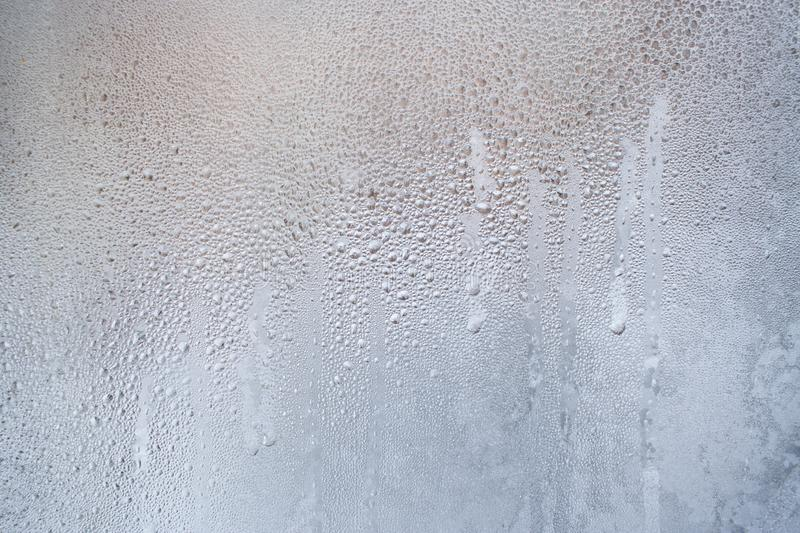 Frozen trickles and water drops on the winter window as background. Frozen trickles and water drops on the winter window as background or wallpaper. Natural ice royalty free stock photo