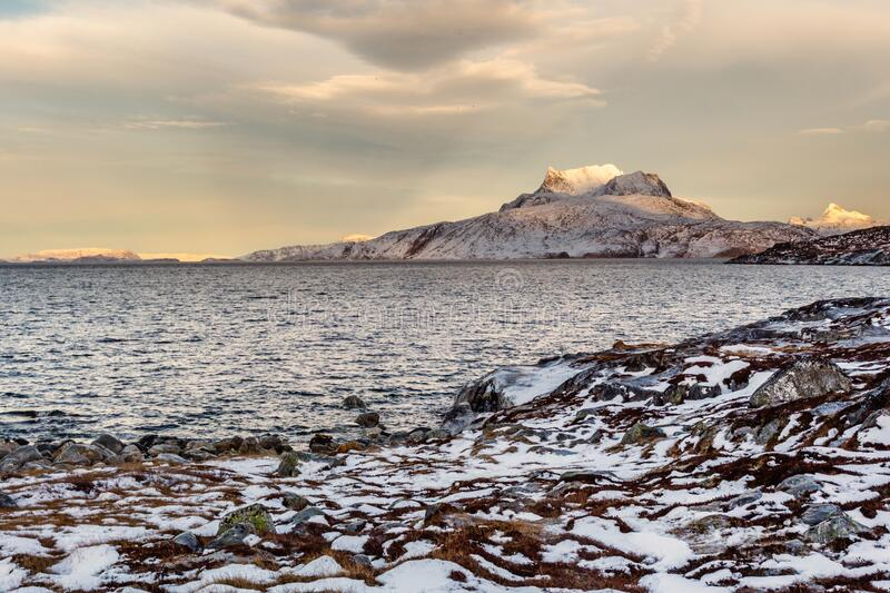 Frozen tundra landscape with cold greenlandic sea and snow Sermitsiaq mountain in the background, nearby Nuuk city, Greenland stock image