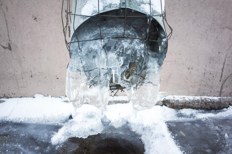 Frozen urban downspout full of ice stock photo