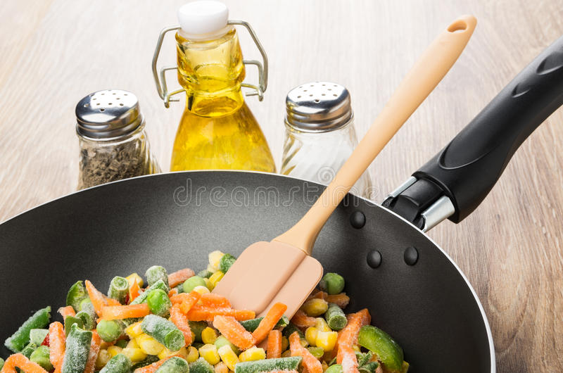 Frozen vegetable mix in frying pan, oil, salt, pepper. Frozen vegetable mix in frying pan, bottle of oil, salt, pepper on wooden table stock photo