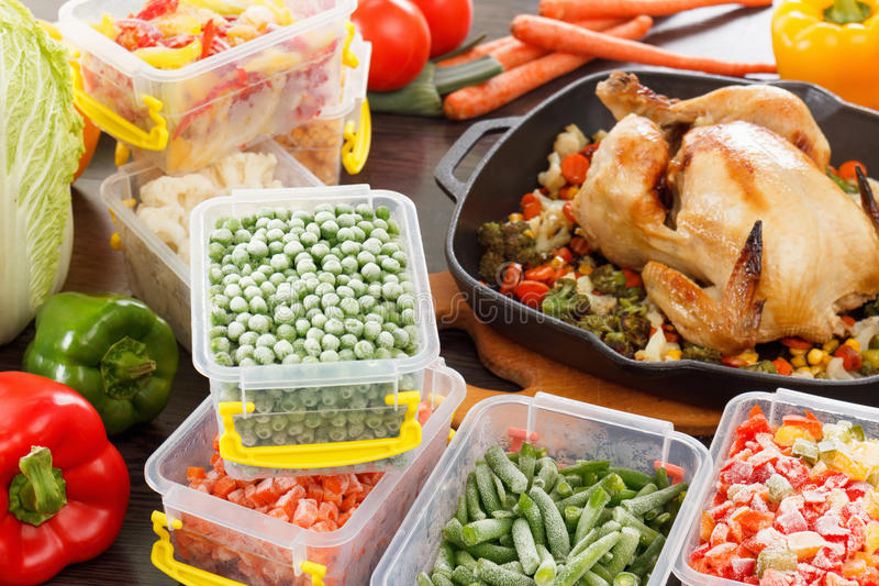 Frozen veggies nutrition and roasted chicken food. Frozen veggies nutrition in plastic containers, roasted chicken in pan. Healthy freezer food royalty free stock photo