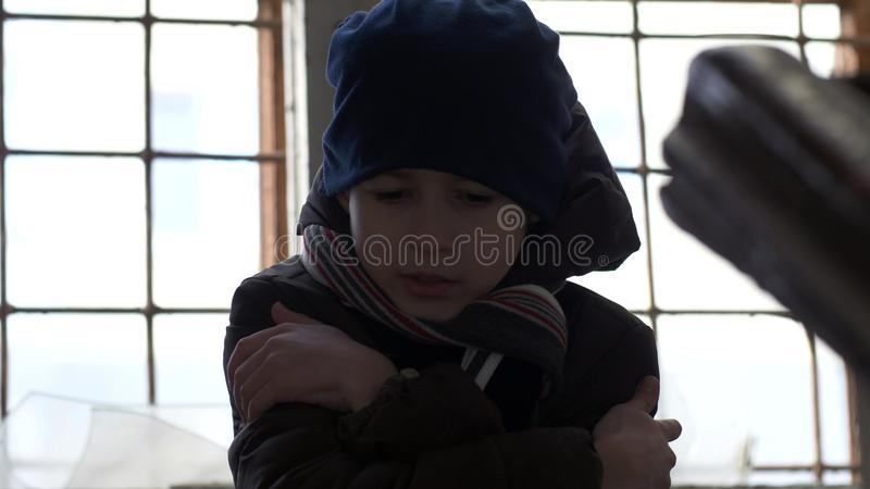 Frozen wary boy is warming in a dilapidated old house, boy standing near a broken window. Have fun royalty free stock photos