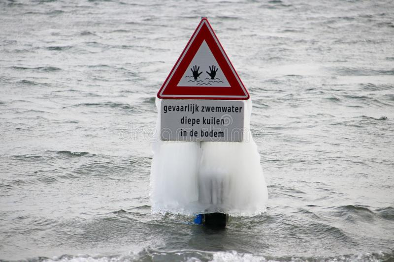 frozen water as ice, created by wind and waves at Zevenhuizerplas in Oud Verlaat, the Netherlands on warning sign for deep stock photography
