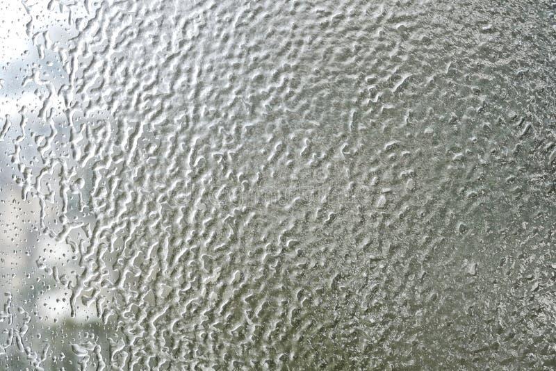 Frozen water drops. On a car window stock image