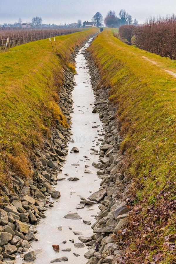 Frozen water of irrigation canal. Frozen water of irrigation channel in the countryside of Emilia Romagna in Italy stock images