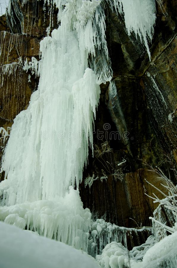 Frozen waterfall among the rocks. The waterfall is freezing, huge icicles. Ice white and blue. Winter waterfall. Russia. stock images