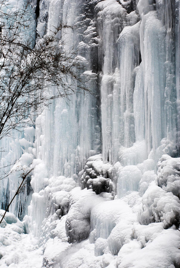 Frozen waterfall and Snow. Ice formation from a frozen waterfall above a cave. Photo taken in Tiger Tooth scenic, Sichuan, China. Tiger Tooth is still unexplored stock photography