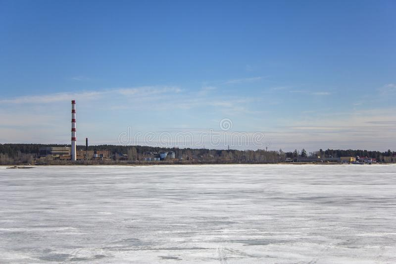 Frozen white snow lake on the background of a plant with a striped red pipe, buildings and warehouses in a green forest under a. A frozen white snow lake on the royalty free stock photos