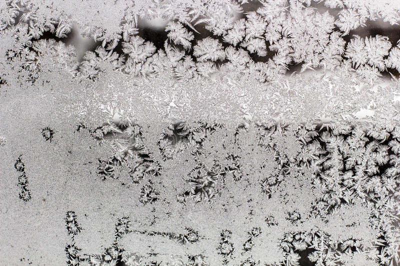 Frozen window glass with frost patterns. On a cold winter royalty free stock image