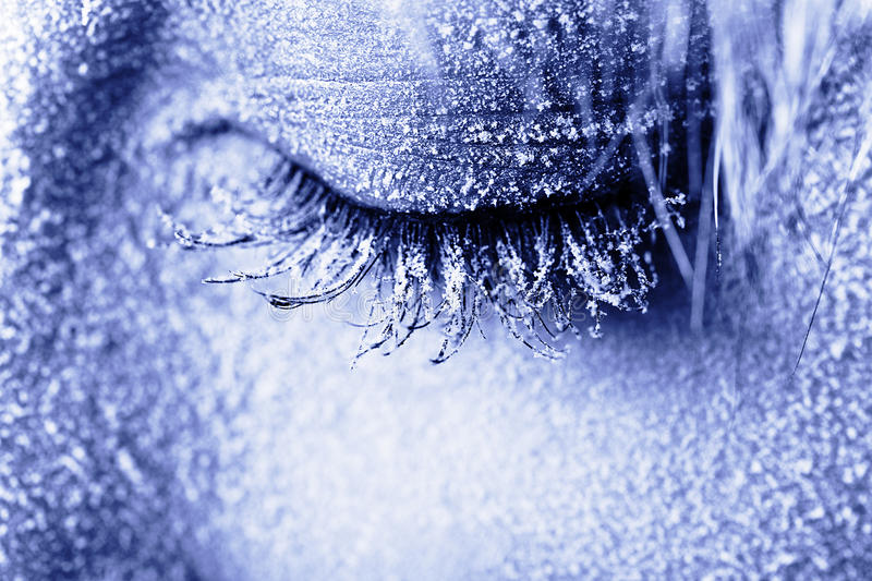 Frozen woman's eye covered in frost. Close-up shot toned in blue