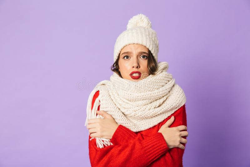 Frozen woman wearing winter hat and scarf isolated over purple background. Portrait of a young frozen woman wearing winter hat and scarf isolated over purple stock photos