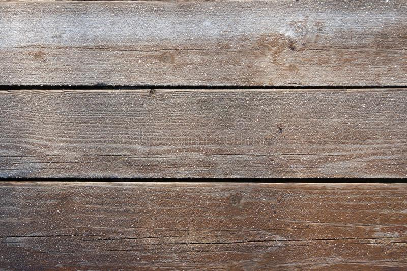 Frozen wood boards background. It is real foto in sunny frosty day stock image