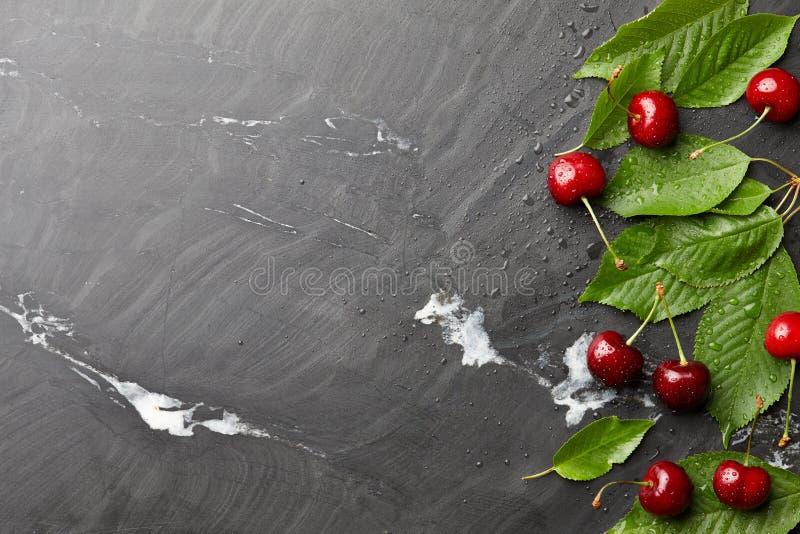 Frsh słodkie wiśnie z liśćmi na czerń kamieniu obraz royalty free